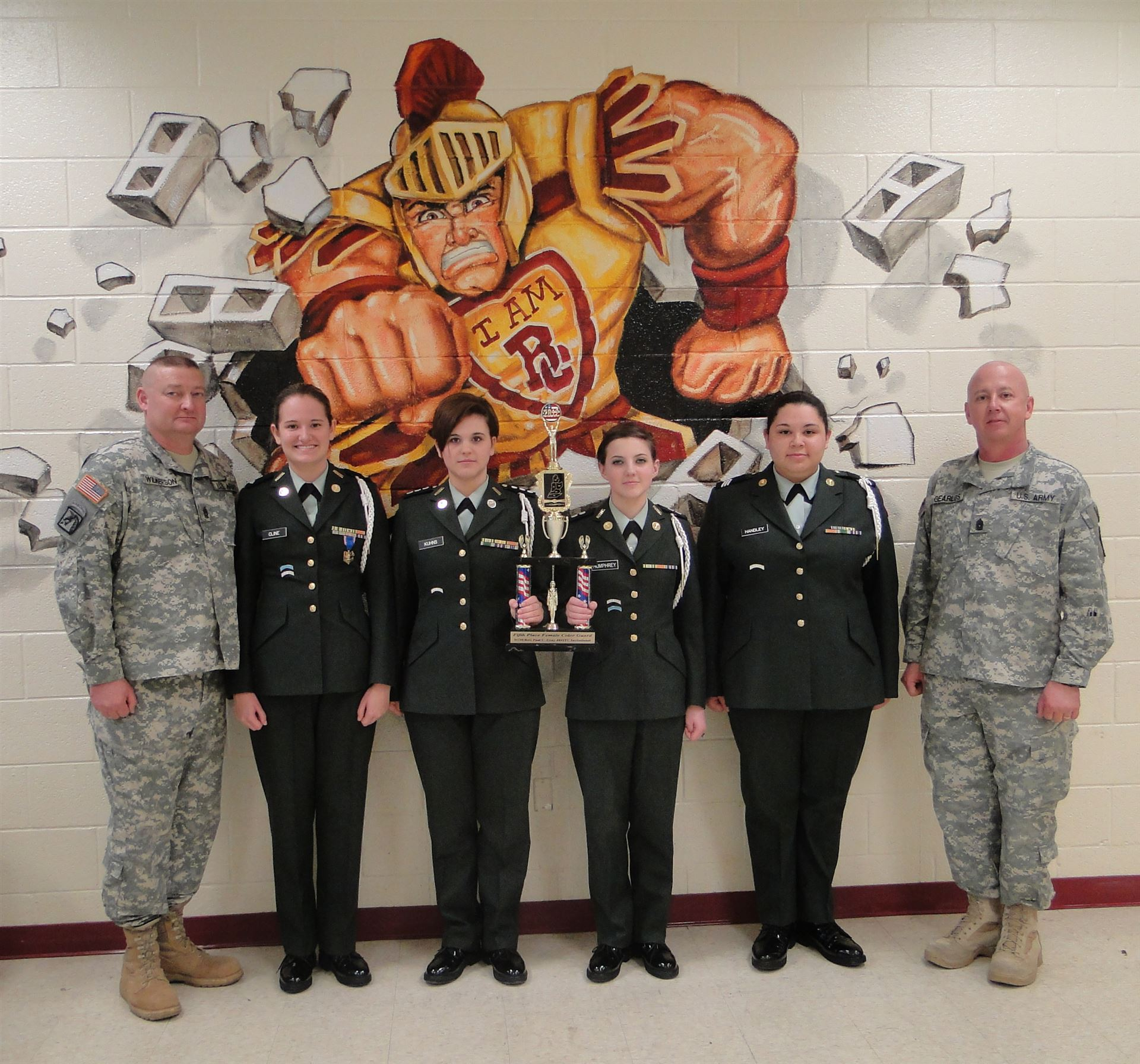 JROTC officers in front of trojan sign